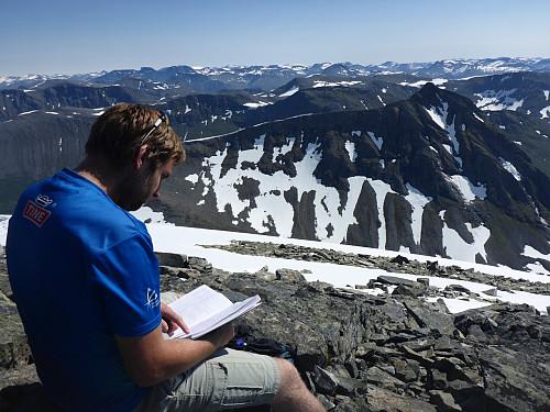 Kroksleiven studerar gjesteboka - ikkje så mange som er opp her samanlikna med naboane. Neste turmålet, Tverrfjellet, i bakgrunnen.