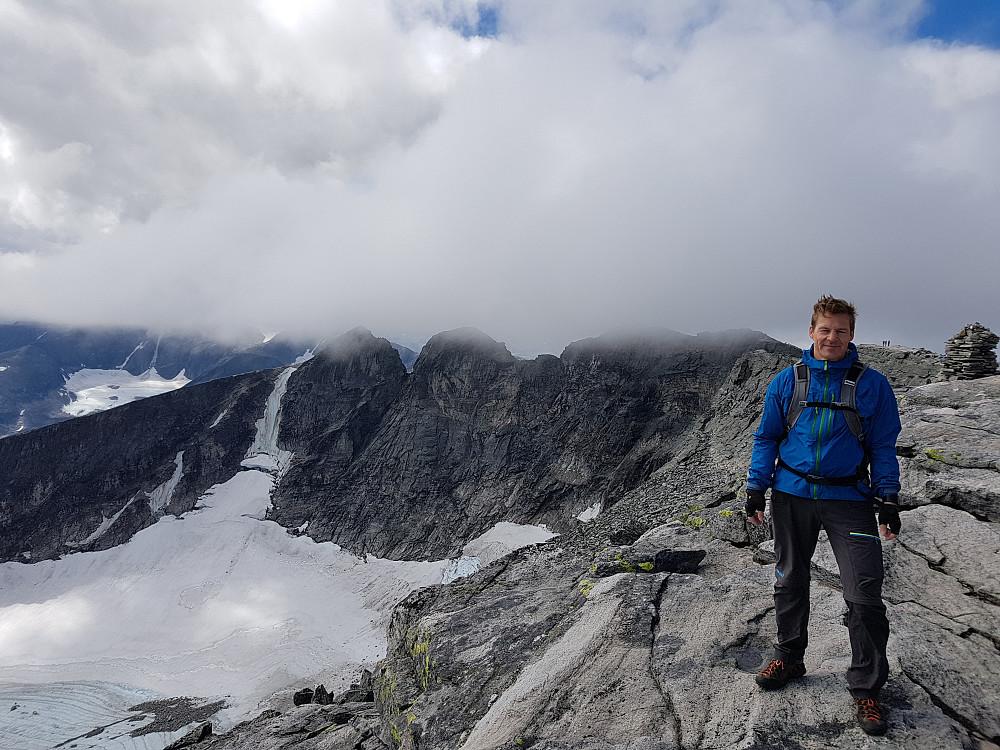 Her er Einar på Stortoppen. I skodda bak ligg Midttoppen og toppen til venstre er Vest toppen, 2253 moh. Planen vår er å gå ned att til elva på ca 1630 moh, krysse den og så gå opp att til Vest toppen....