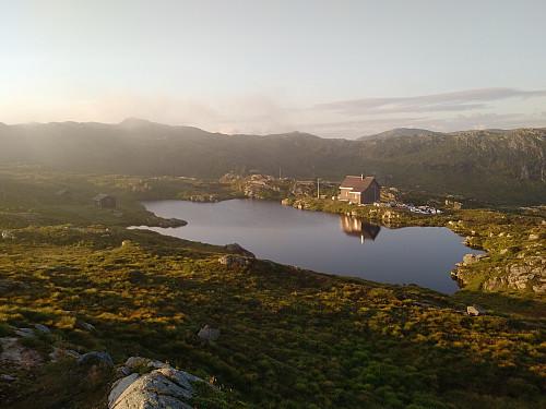 """Utsikt fra """"Stormfuglen"""" mot Breidablikk (til venstre) og Djervhytten (på andre siden av vannet)."""