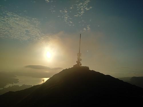 Ulriken vest med Ulriksmasten med lav kveldssol i bakgrunnen.
