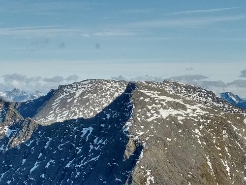 Sørtoppen av Trollvasstinden (1422 m.o.h.) omtrent midt i bildet, og med fjellryggen som fører mot midt-toppen (litt utenfor venstre billedkant). Bak sees deler av Litlevasstinden, og i det fjerne sees Trolltindan i Rauma med bl.a. Trollryggen, Bruraskaret og Store Trolltinden.