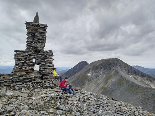 Lunchpause ved varden på toppen av Remmemstinden. Ferden videre går over Ytstetinden og Trolltinden, som sees i bakgrunnen.