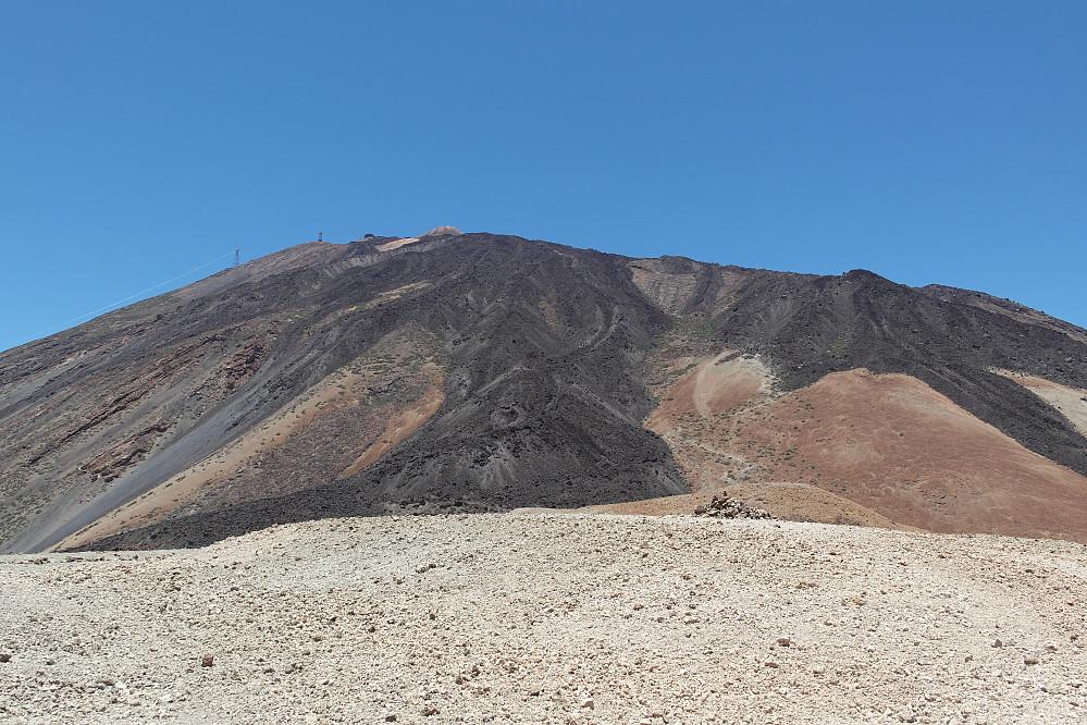 Stien videre oppover kan skimtes til høyre for den svarte lavaryggen midt i bildet. Refugio Altavista sees så vidt langt der oppe.