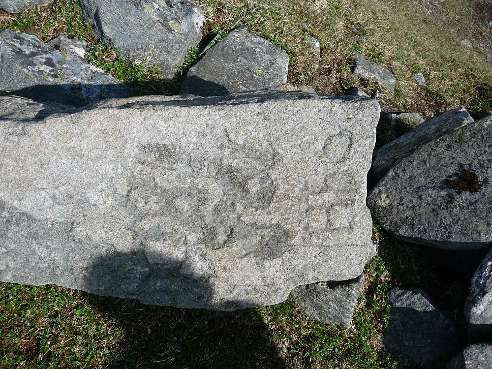 En stein i gjerdet med diverse tall på