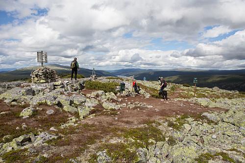 Jevn strøm av folk på toppen en finværsdag i august.