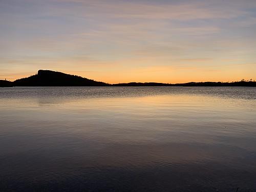 Idyllisk solnedgang over vannet.