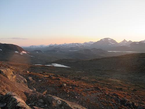 Nedstigning fra Nordre Svartdalspiggen mot solnedgangen og tindene i nordvest. Sjoghols- og Mjølkedalstinden dominerer til høyre