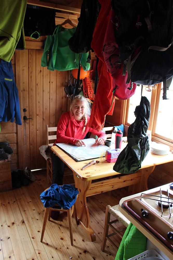 Astrid studerer kart og planlegger topptur mens klærne tørker.