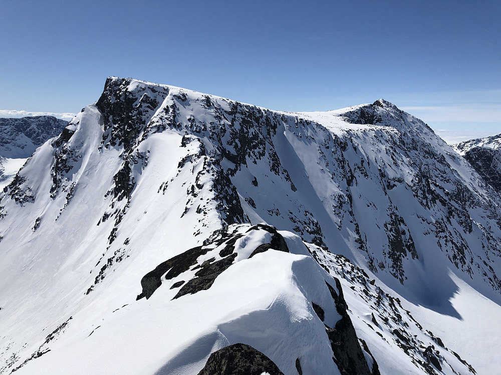 Vel oppe på Søre etter en tung oppstigning fra skaret mellom Søre og Midtre. Sva med snø og is innimellom. Utsikt mot Skarvflyløyfttind og Austre Leirungstinden stikkende opp bak til høyre.