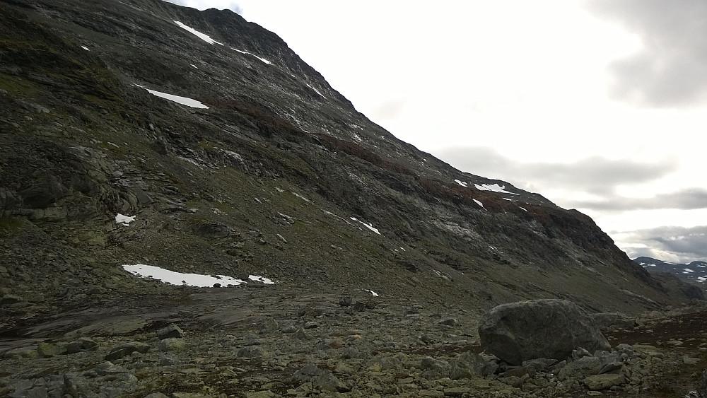 """""""nordover fjellsiden i retning en nokså flat utløper i karakteristisk rødfarget stein, på ca. 1560 moh"""" Denne røde rampa i sørvestflanken på Uranostinden er lett å identifisere fra Urdadalsbandet."""