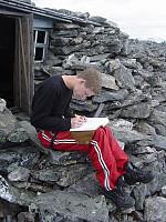 Sondre skriver seg inn i boka på toppen, ved hytta til Heen.