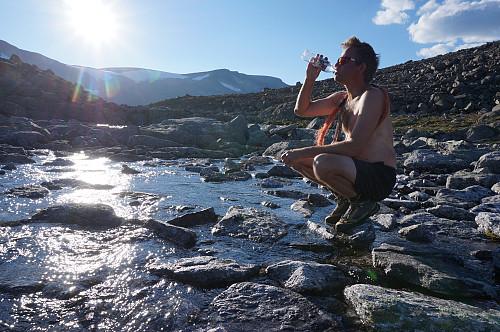 Varm dag, her slukker Egil tørsten fra elva mellom Styggvatnet og Storvatnet.