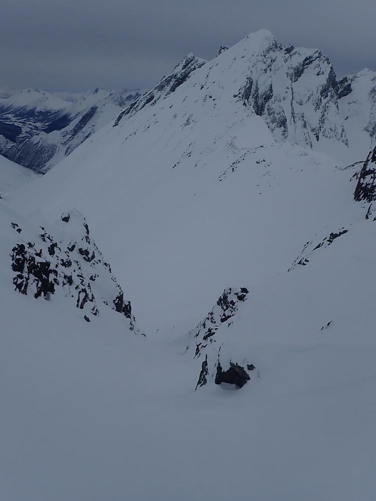 Da vi ankom Gullmorhornet var klokka blitt 1535, og vi begynte å få litt knapt med tid om vi skulle rekke å gå innom Vellesæterhornet (som sees midt i bildet her). Jeg gjorde en kort rekognoseringstur langs eggen, men konstaterte at det var rapellterreng allerede etter snaue 20 meter. Jeg tok så en liten runde sørover og fant da ei renne som så ut som den kunne ta oss ned i dalen på sørsida. Vi ble enige om å prøve renna og at Vellesæterhornet fikk vente til en annen dag. Fin skikjøring ned her, riktignok på litt hardt underlag.