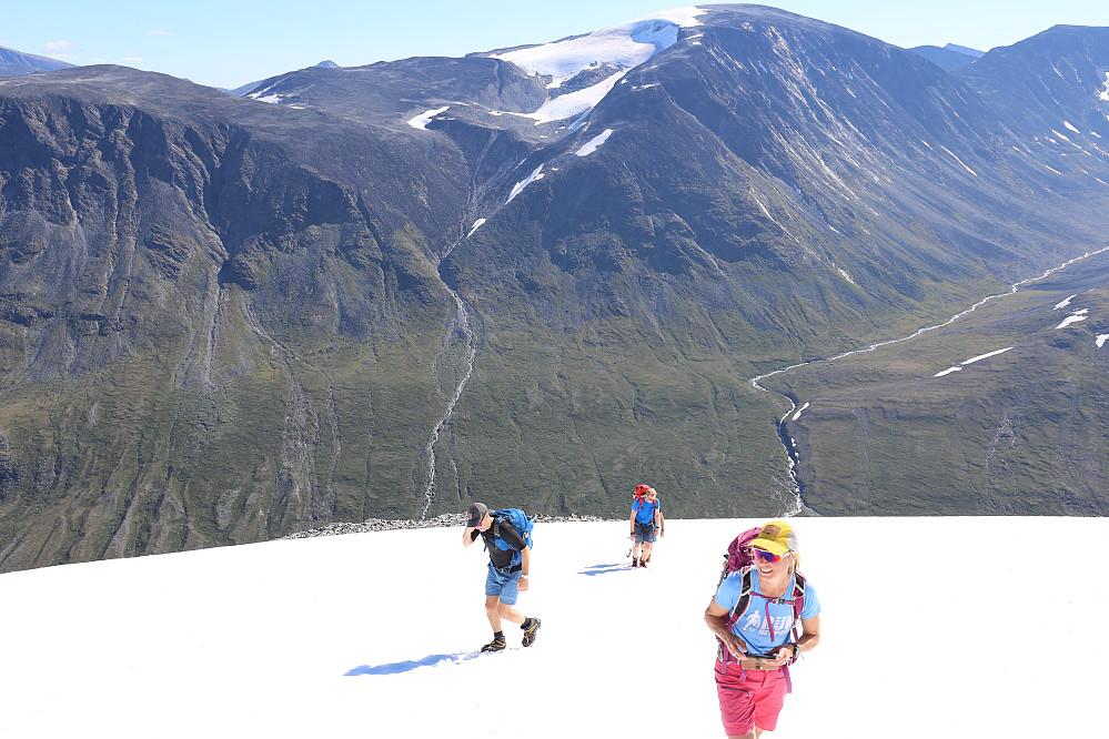 Marianne gliser mens Nils-Jørgen og Arne kommer luntende bakfra. Leirhø i bakgrunnen.