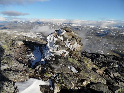 Varden på Liabrekulen. Skyer over Jotunheimtoppane i bakgrunnen.