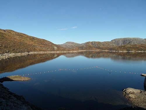Speilblank morgon på Nilsebuvatnet. Ein ser inntaksvirvel i vatnet t.h.