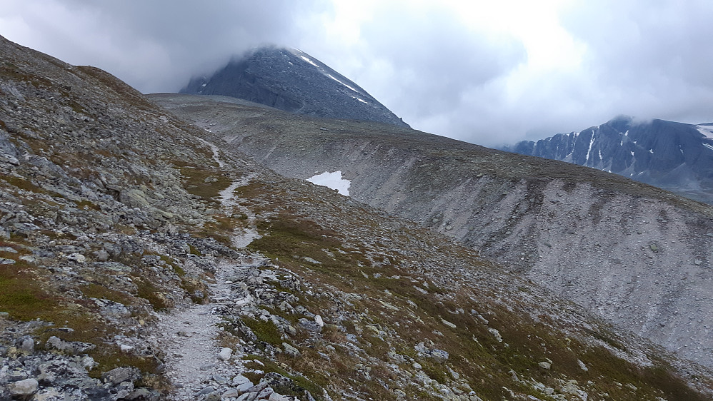 Trolltinden med tåke. Ruta ned på nordsiden er brutal med store blokker som kan være slitsomme å forsere. Bildet viser stien øverst i dalen, der den har svingt av fra Dørålen i retning Langholvatnet.