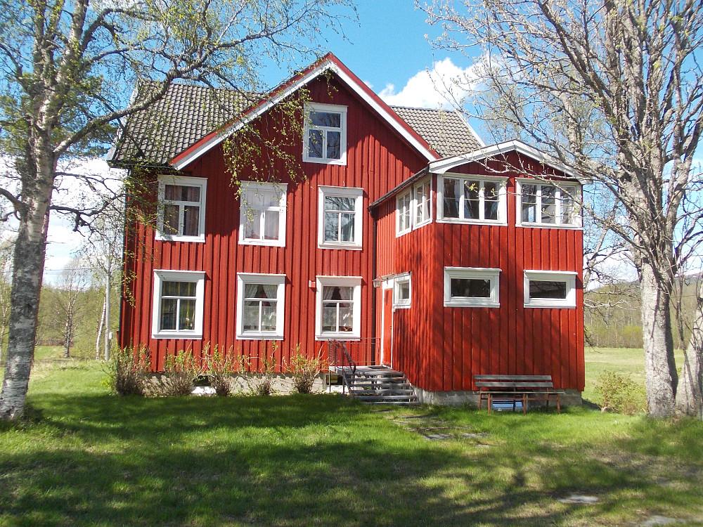 Parkering på gårdsplassen ved denne røde stugan i Sulåmo